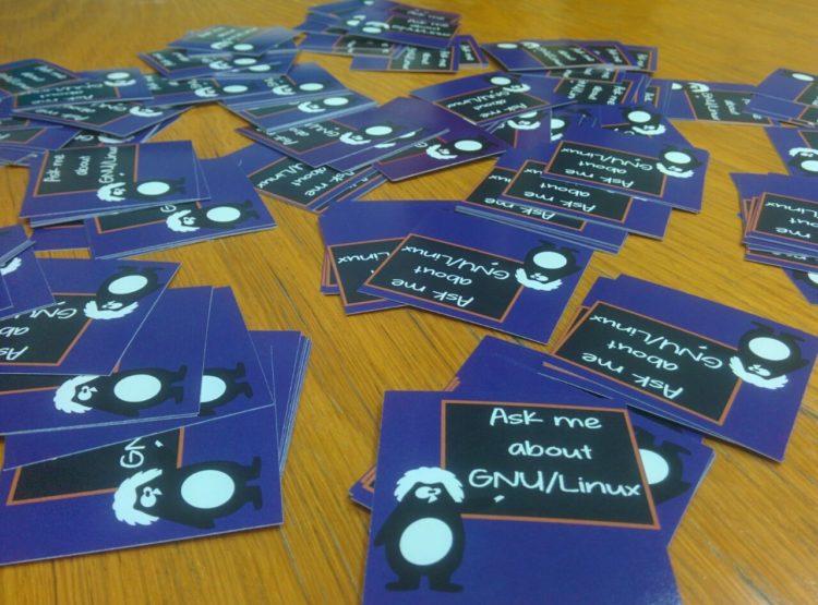 Stickers ask me about GNU/Linux sparsi su un tavolo alla Casa del Quartiere